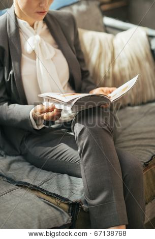 Closeup On Business Woman Reading Magazine While Sitting On Diva