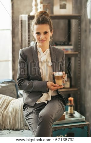Portrait Of Business Woman With Coffee Latte Sitting On Divan In