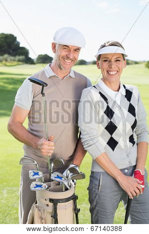Golfing couple smiling at camera on the putting green on a sunny day at the golf course