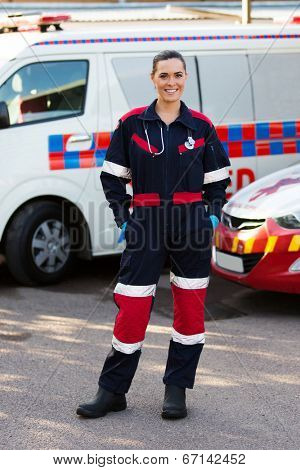 happy emergency medical service worker standing in front of ambulance