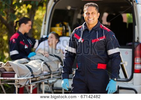 handsome paramedic with colleague and patient on background