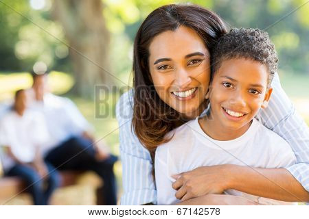 happy indian mother hugging her son in front of family outdoors