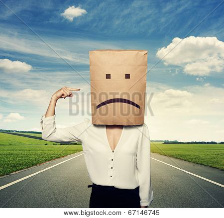 concept photo of bad mood. woman with paper bag on the head