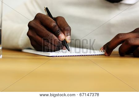 Closeup portrait of a male hand writing on a paper