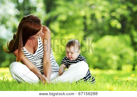 Mother and daughter sitting on grass in spring park