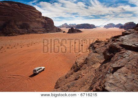 White Car Between The Mountains In Wadi Rum, Jordan.