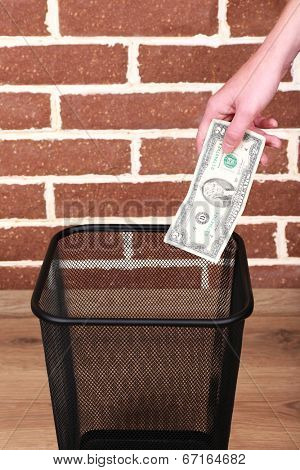 Throwing away your money on brick wall background
