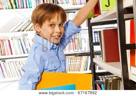 Happy schoolboy searching books in library
