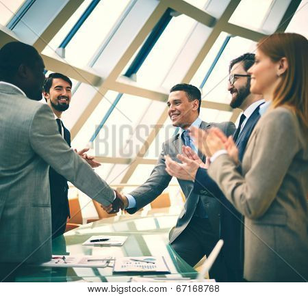 Two successful businessmen handshaking while their colleagues congratulating them