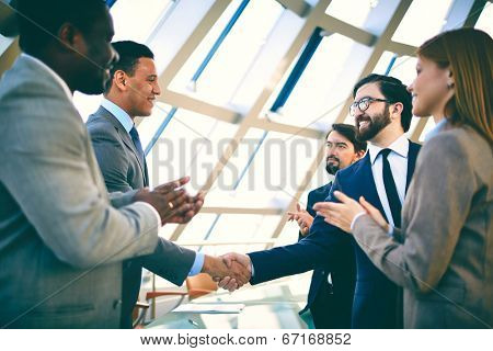 Two successful businessmen handshaking while their colleagues clapping their hands