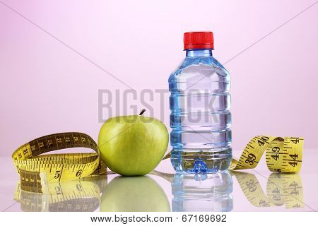 Bottle of water, apple and measuring tape on purple background