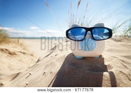 Holiday savings piggy bank on a beach vacation with sunglasses