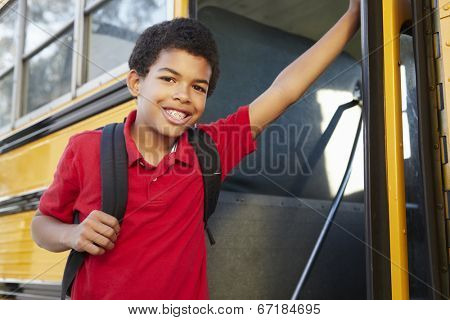 Pre teen boy getting on school bus