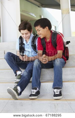 Pre teen boys with phone at school