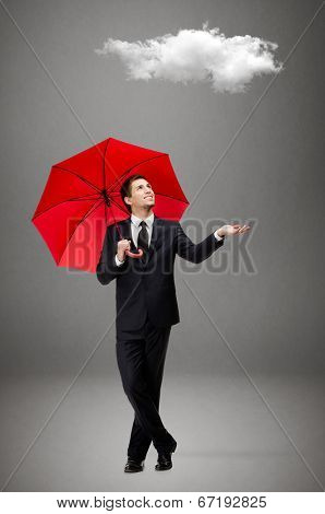 Palming up man with opened umbrella checks the rain and looks at the cloud overhead, isolated on grey