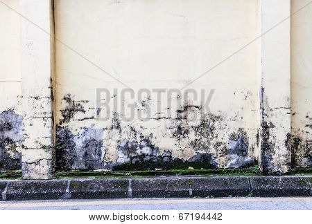 Paint peeling off dirty concrete wall