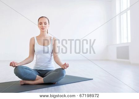 Young woman doing yoga in studio