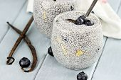 stock photo of mango  - Chia seed pudding made with mangos and blueberries with extreme shallow depth of field - JPG