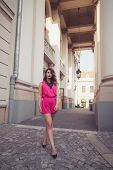 stock photo of jumpsuits  - Fashion glamorous and attractive woman dressed in a sexy sleeveless pink jumpsuit walking on imaginary catwalk on street - JPG