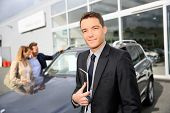 image of 35 to 40 year olds  - Smiling car dealer standing by vehicle - JPG