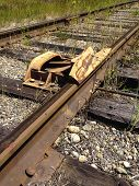stock photo of railroad car  - A train car derailment device is attached to railroad tracks to keep drifting cars from rolling and causing damage by derailing the car off the tracks - JPG
