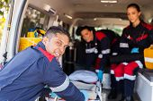stock photo of stretcher  - paramedic team pulling stretcher out of an ambulance - JPG