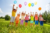 picture of balloon  - Happy kids with balloons and arms up in the sky in green field - JPG