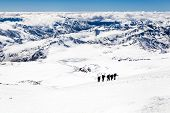 picture of blue ridge mountains  - People hiking silhouette and climbing on snow in high mountain Elbrus landscape in autumn or winter Caucasus Mountains in Russia and Georgia - JPG