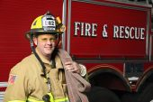 pic of firehose  - smiling firefighter standing in front of fire engine in uniform holding a fire hose and wearing a helmet - JPG