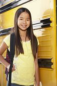 stock photo of pre-teen girl  - Pre teen girl with school bus - JPG
