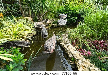 Wooden Fish On A Stick As A Decoration In A Chanel In The Park Among Tropical Green Plants