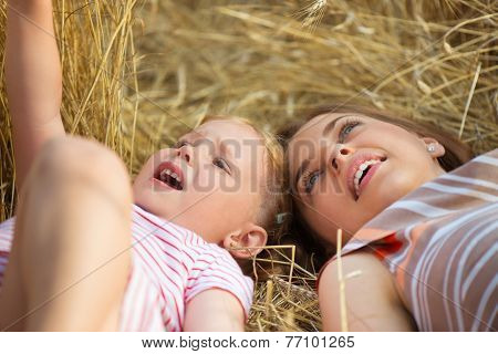 Cute Little Girl With Young Mother Lying In Wheat Field