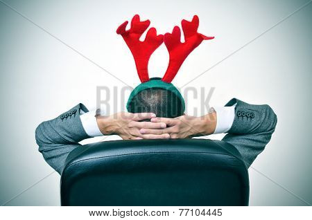 a man with a reindeer antlers headband relaxing in his office chair after an office christmas party