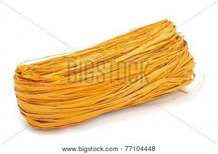a skein of natural raffia dyed yellow on a white background
