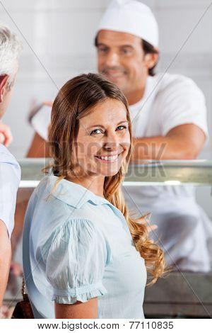 Portrait of happy woman standing in butcher's shop