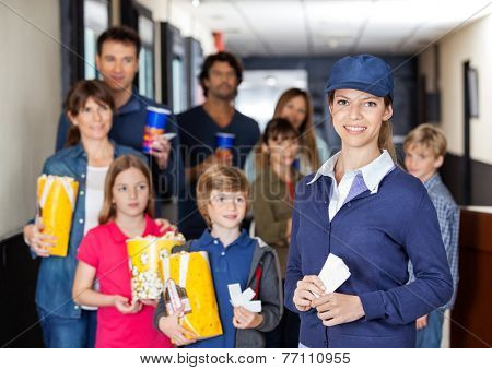 Portrait of happy female worker with families holding snacks in background at cinema