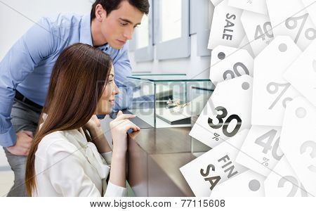 Girl with man chooses expensive jewelry at jeweler's shop on sale. Concept of wealth and luxurious life