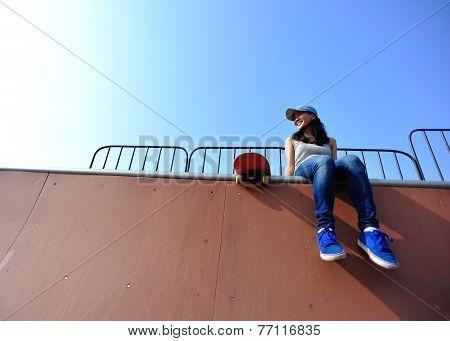 young asian woman skateboarder sit at skatepark