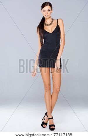 Full Length Portrait of Long Hair Young Woman Posing in Sexy Black Fitting Dress on Gray Background.