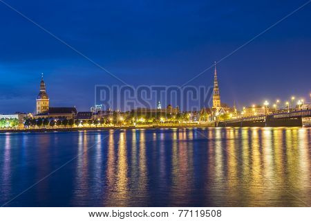 Skyline of Riga seen across the river Daugava after the sunset. The tallest building on the picture is the St. Peter's Church