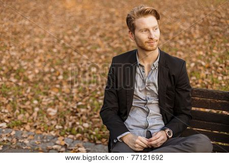 Young Man At The Bench In Autumn Park