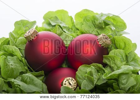 Fresh Green Salad With Three Red Christmas Ball's, Isolated On White