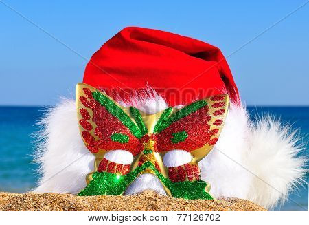 Christmas Hat With Glittering Carnival Mask On The Seashore