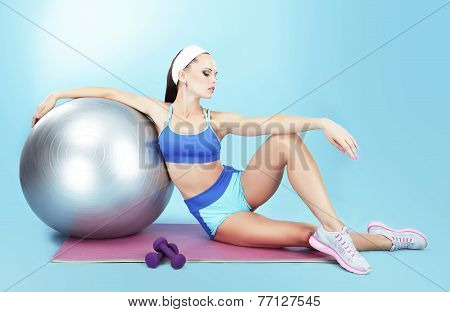Repose. Sportswoman With Sport Equipment - A Fitness Ball And Dumbbells