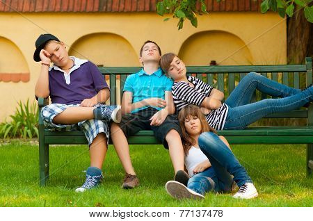 Bored teenagers sitting and lying on the bench on beautiful spring day