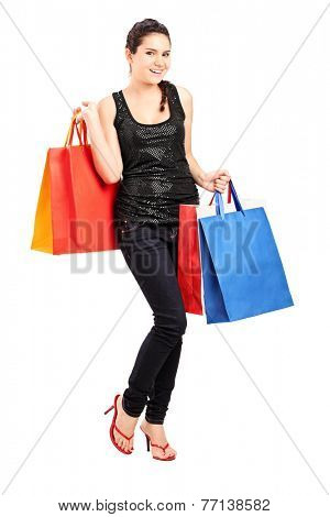 Full length portrait of a fashionable female holding bunch of shopping bags isolated on white background