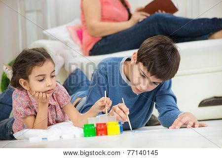 Two Children Painting With Colorful Paints At Home