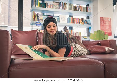 Beautiful Young Brunette Reading Book In A Bookstore