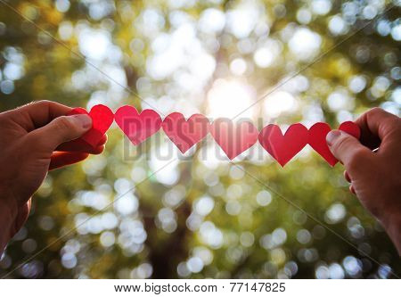 hands holding a string of paper hearts up to the sun during sun