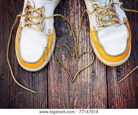 a pair of deck shoes on a nice wooden porch with the laces in a heart shape